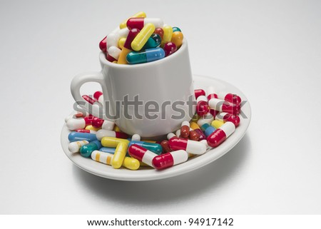 cup filled to overflowing with medical capsules - stock photo