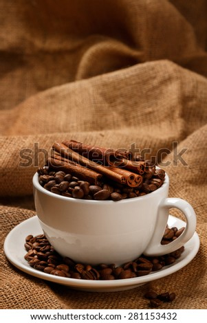 Cup filled with coffee beans against a sackcloth surface