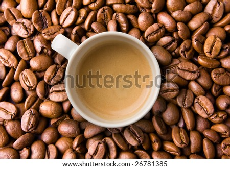 Cup filled with Espresso top view on coffee beans - stock photo
