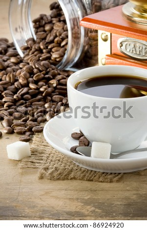 cup full of coffee drink on roasted beans at wooden background - stock photo