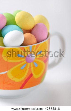 Cup full of colored easter eggs on a white background - stock photo