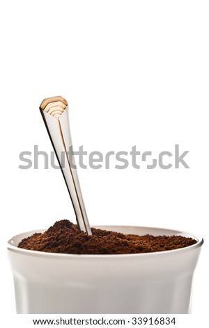 Cup full of ground coffee with a spoon in it, isolated against a white background