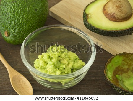 Cup mashed avocado. and avocado pieces on a wooden floor. - stock photo