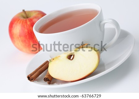 Cup of apple tea with cinnamon on white background. Shallow dof - stock photo