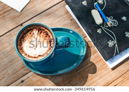 Cup of art latte or cappuccino coffee in working place - stock photo