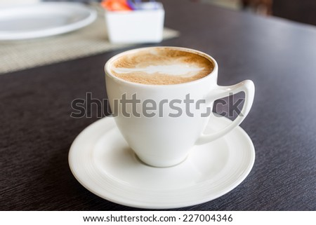 Cup of art latte or cappuccino coffee on a wooden table