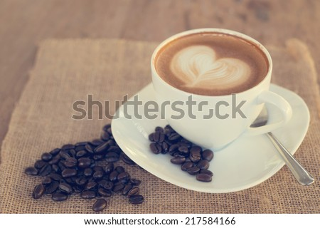 Cup of art latte or cappuccino coffee with vintage filter effect - stock photo