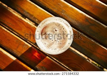 Cup of beer in garden restaurant - stock photo