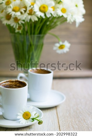Cup of black coffee and daisy flowers on the old table - stock photo