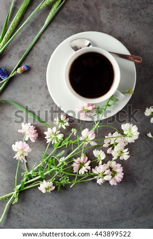 Cup of black coffee, espresso set with wild flowers, on grey grunge background. Simple things in life and summer leisure concept. World concentrated in a cup. - stock photo