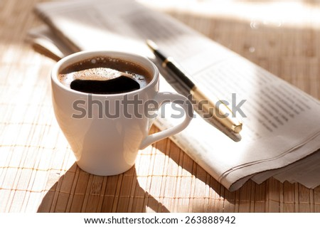 Cup of black coffee, newspaper and a pen on the table in the morning - stock photo