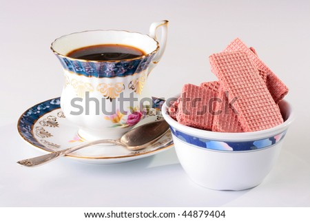 Cup of black coffee on a saucer with a spoon and wafers in ceramic ware.