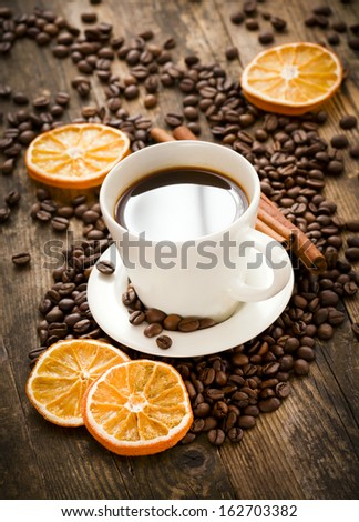 Cup of black coffee surrounded by roasted coffee beans and orange sl
