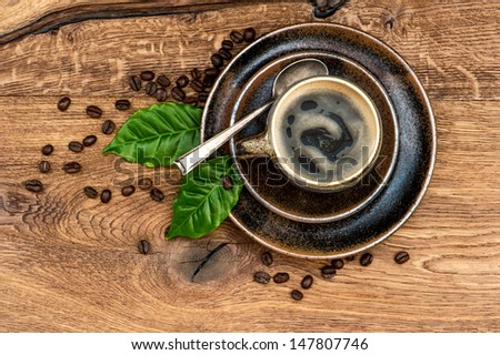 Cup of black coffee with beans and leaves on wooden table. Top view - stock photo