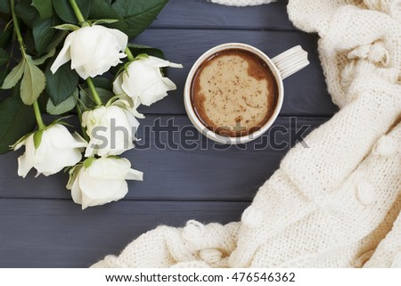Cup of black coffee with milk or cream, white knitted plaid and white roses, on white wooden 
