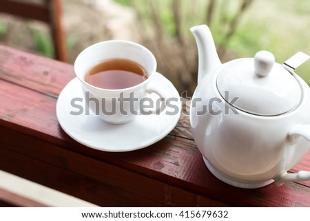 Cup of black tea and kettle on veranda - stock photo