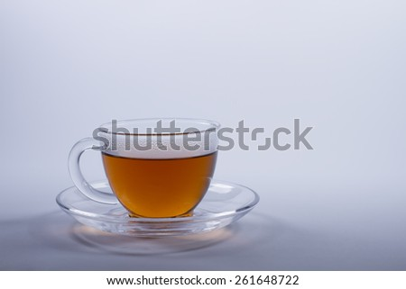 Cup of black tea in a glass cup with a saucer. - stock photo