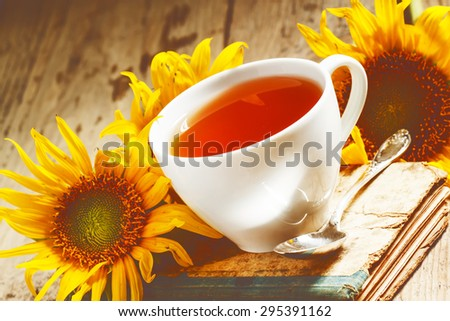 cup of black tea, sunflowers, old books on wood background, selective focus
