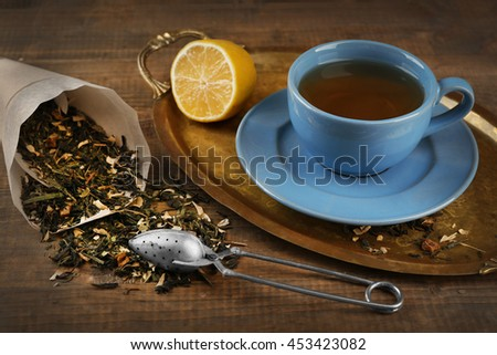 Cup of black tea with lemon on wooden table