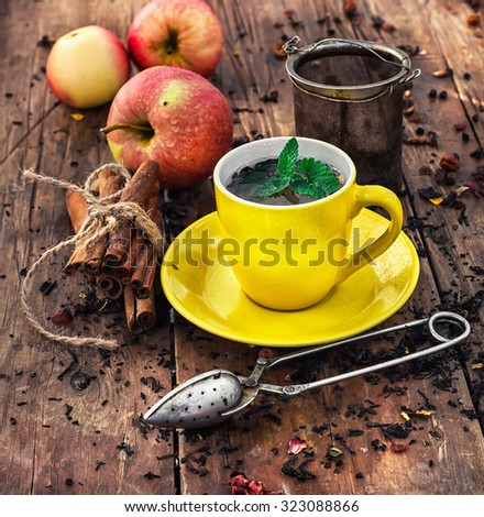 Cup of brewed herbal tea on wooden background strewn with tea leaves - stock photo