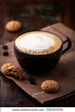 Cup of cafe au lait and biscotti on the table - stock photo