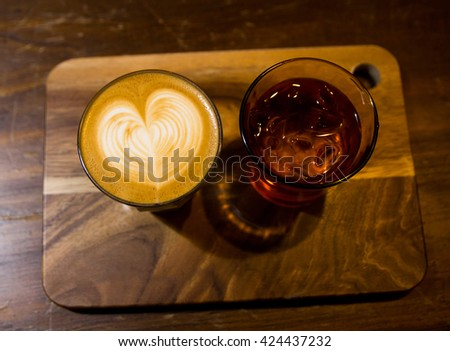 Cup of cappuccino art coffee with froth shape heart and wooden background - stock photo