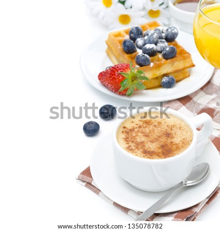 cup of cappuccino, belgian waffles with blueberries and strawberries, orange juice for breakfast isolated on a white background - stock photo