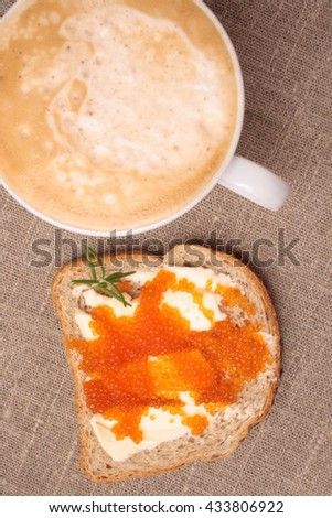 Cup of cappuccino coffee and sandwich with oil and red caviar