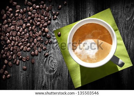 Cup of cappuccino coffee, green napkin and beans on black wooden table, top view - stock photo
