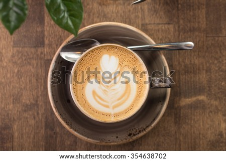 Cup of cappuccino coffee isolated on wooden background - stock photo
