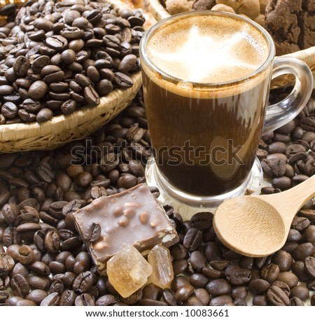 Cup of cappuccino coffee, surrounded by coffee beans, cookies, crystallized brown sugar and chocolate. - stock photo