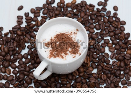 Cup of cappuccino coffee with beans on wood table - stock photo