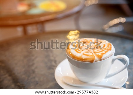 Cup of cappuccino on the table in coffee shop  - stock photo
