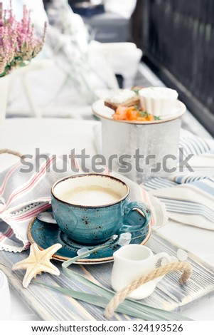 Cup of cappuccino served on vintage wooden tray, with marine style decorations. Natural light toned photo. Salmon sandwiches served on the table. Deck chairs on the background. - stock photo