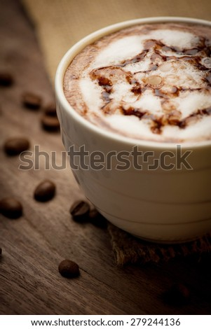 Cup of cappuccino served on wooden table with coffee beans in the background - stock photo