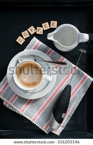 "Cup of cappuccino set with milk blender and letters ""coffee"" on textile napkin, simple setting, overview, natural light photo - stock photo"