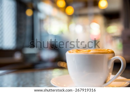 Cup of cappuccino with blur coffee shop background - stock photo
