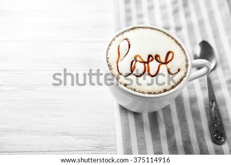 Cup of cappuccino with chocolate syrup and candy on light wooden table - stock photo