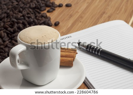 Cup of cappuccino with cinnamon and spilled out coffee beans.  - stock photo