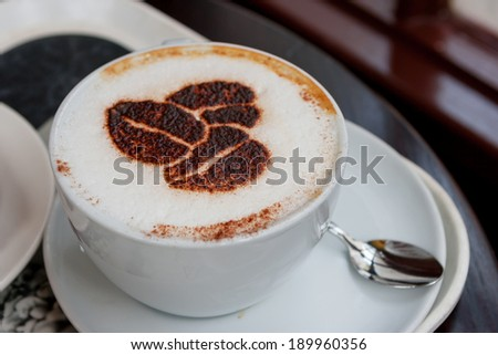 Cup of cappuccino with coffee beans shaped design - stock photo