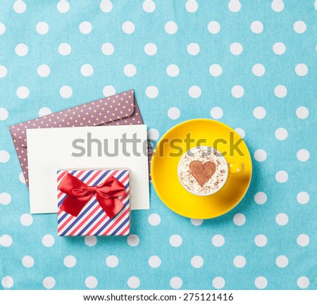 Cup of cappuccino with heart shape and envelope with gift box on blue polka dot background. - stock photo