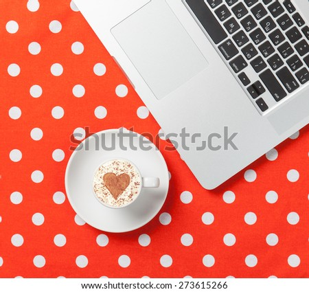 Cup of cappuccino with heart shape and laptop on red polka dot background. - stock photo