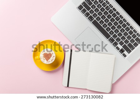 Cup of cappuccino with heart shape and laptop with note on pink background.