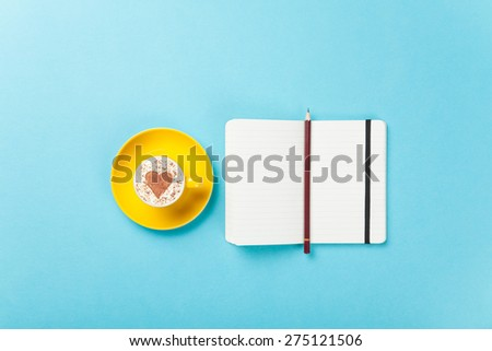 Cup of cappuccino with heart shape and notebook on blue background. - stock photo
