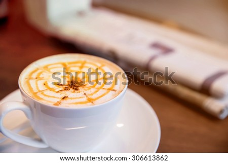 Cup of cappuccino with newspaper on the table, coffee shop background - stock photo