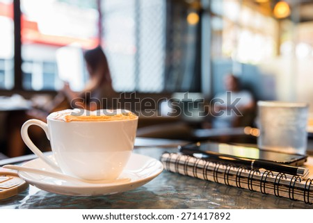 Cup of cappuccino with note book and pen, blur coffee shop background  - stock photo