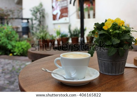 Cup of cappuccino with pansies in a pot on the table. White cup of coffee with spoon on the table outside terrace. Yellow pansies pot aside. Small Italian terrace and patio. - stock photo