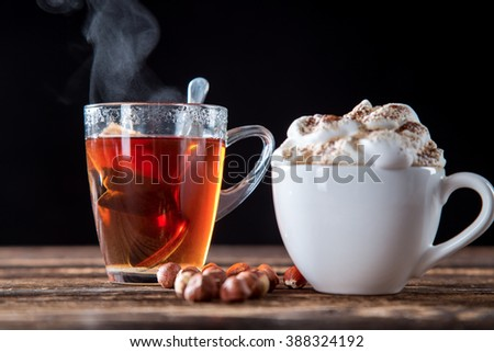 Cup Of Cappuccino With Whipeed Cream And Hot Tea Over Wooden Table, Black Background. - stock photo
