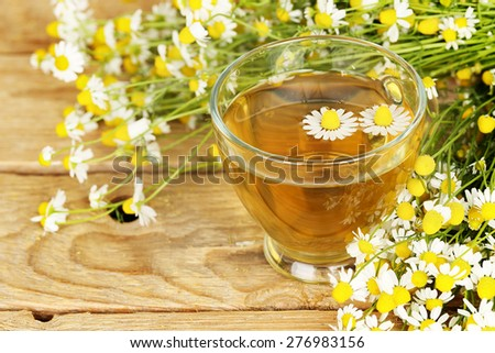 cup of chamomile tea with chamomile flowers on wooden planks - stock photo