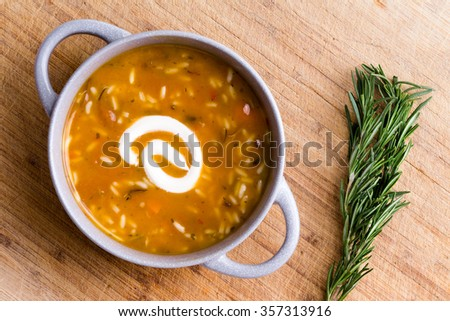 Cup of chicken broth with wild rice served with a twirl of sour cream ready to be garnished with fresh rosemary displayed alongside on a bamboo cutting board, overhead view - stock photo